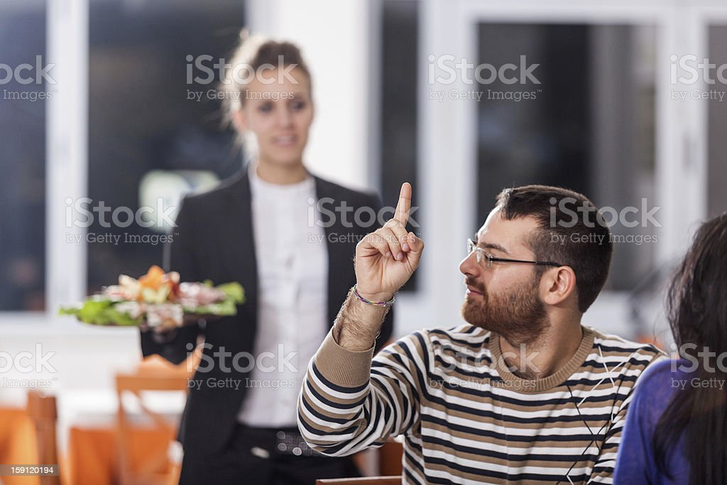 Young Couple at Restaurant with Waitress royalty-free stock photo