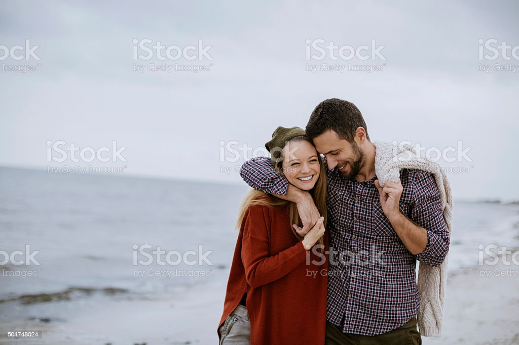 Young couple at the beach stock photo
