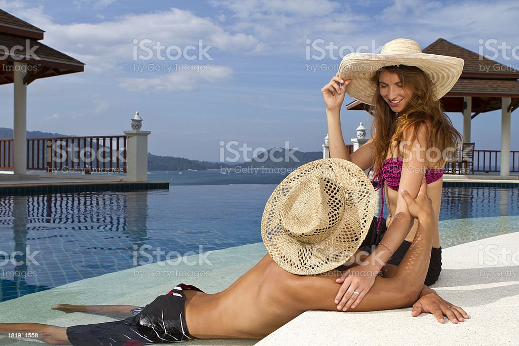 Young couple at the pool of a luxurious resort royalty-free stock photo