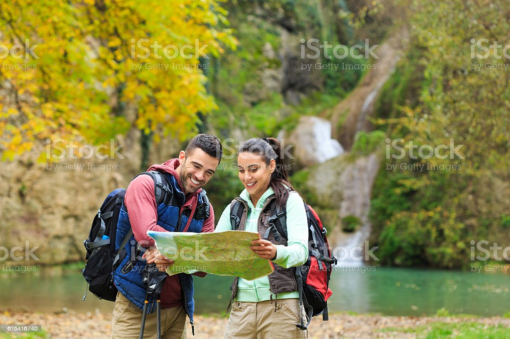 Young couple backpackers using map for finding direction stock photo