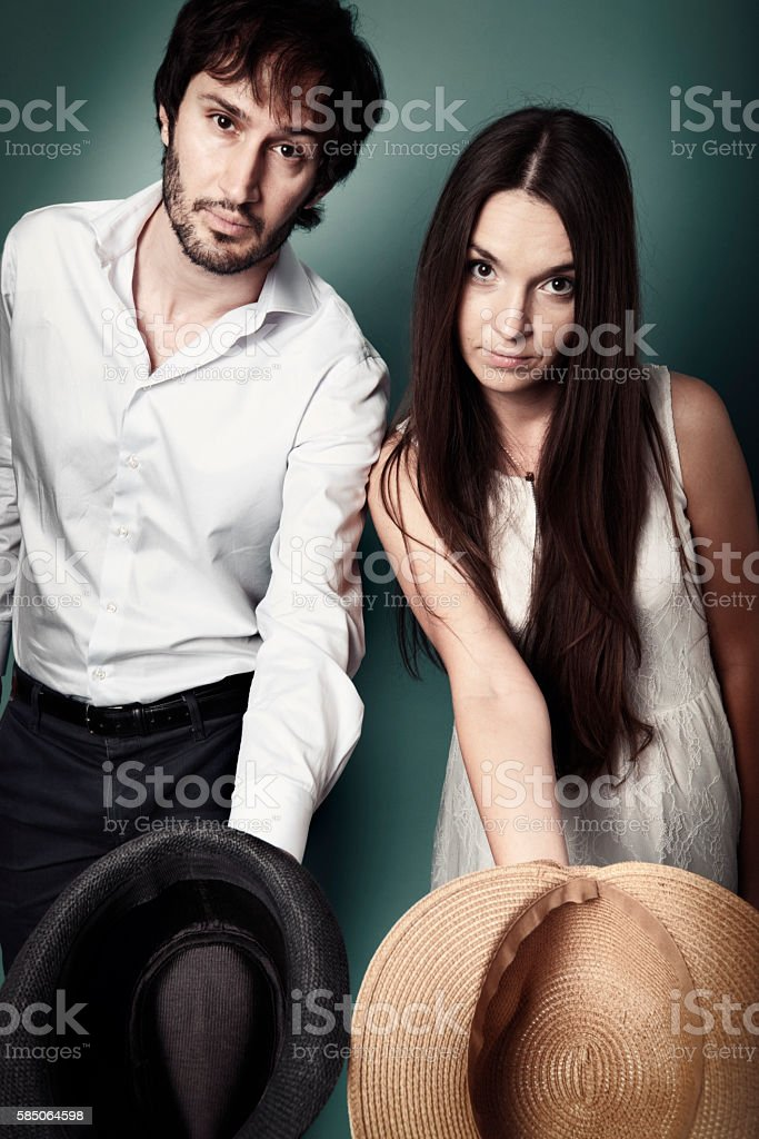 Young couple begs reaching out with a hat stock photo