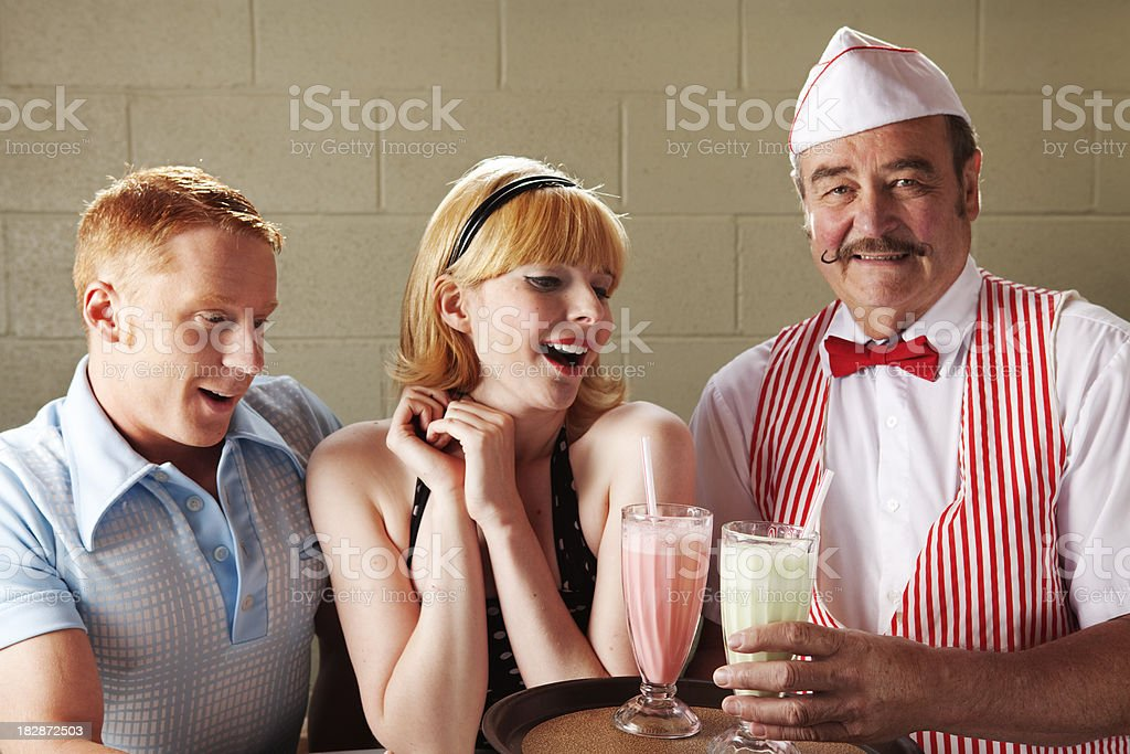 Young couple being served shakes 50s style stock photo