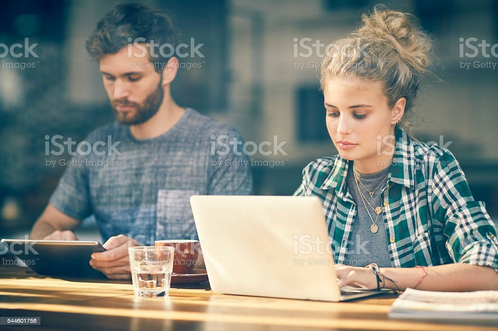 Young couple blogging on tablet an laptop inside cafe window stock photo