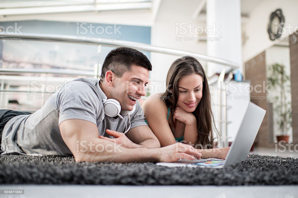 Young couple blogging on the floor stock photo