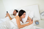 Young couple- both using mobile phones in bed