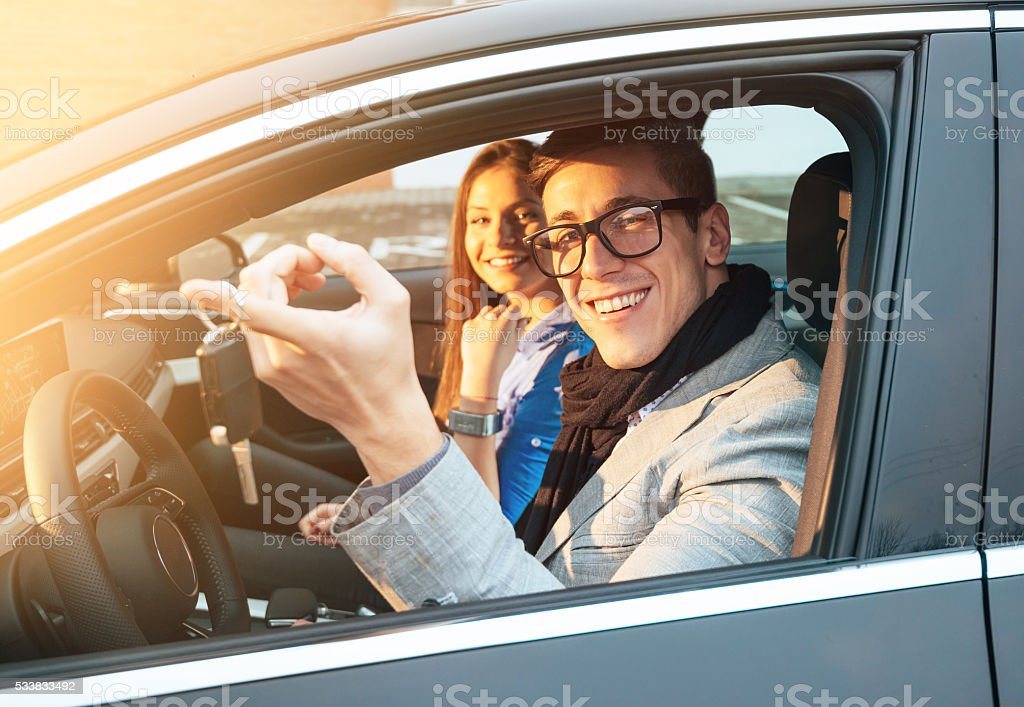 Young couple bought new luxury car and showing keys stock photo