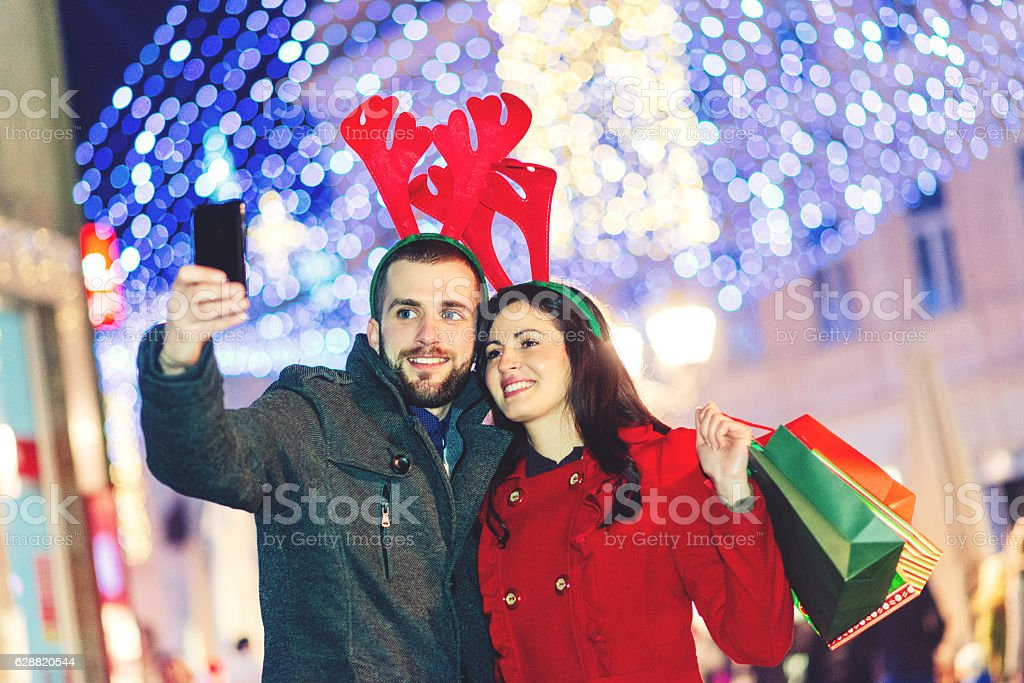 young couple buying christmas gifts and taking selfie royalty free stock photo