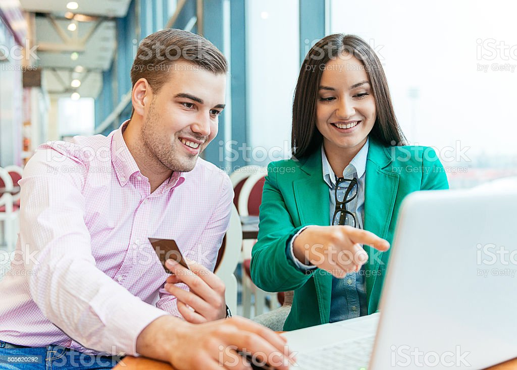 Young couple buying new items on internet auctions and smiling stock photo