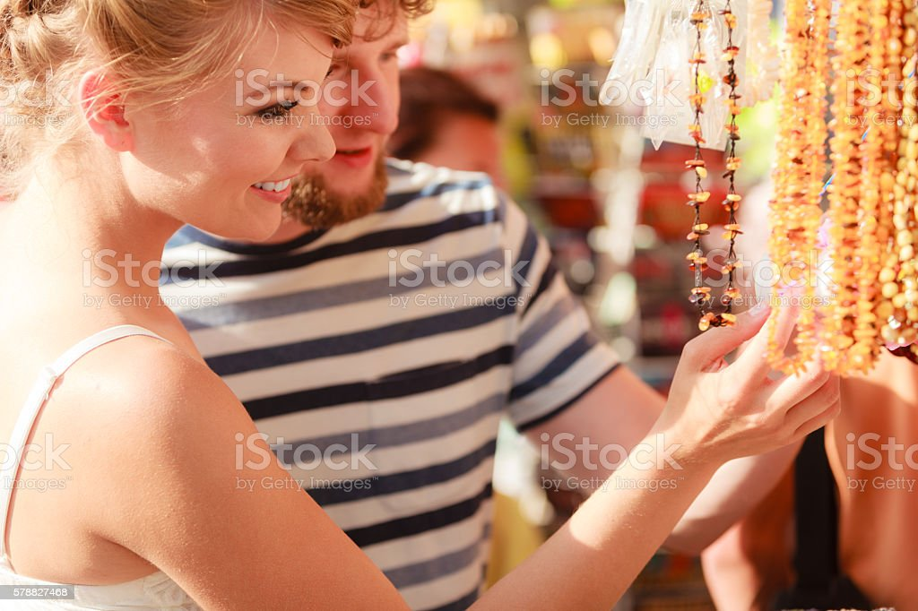 young couple buying souvenirs outdoor stock photo