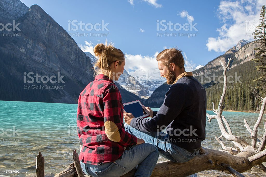 Young couple by the lake consulting digital tablet stock photo