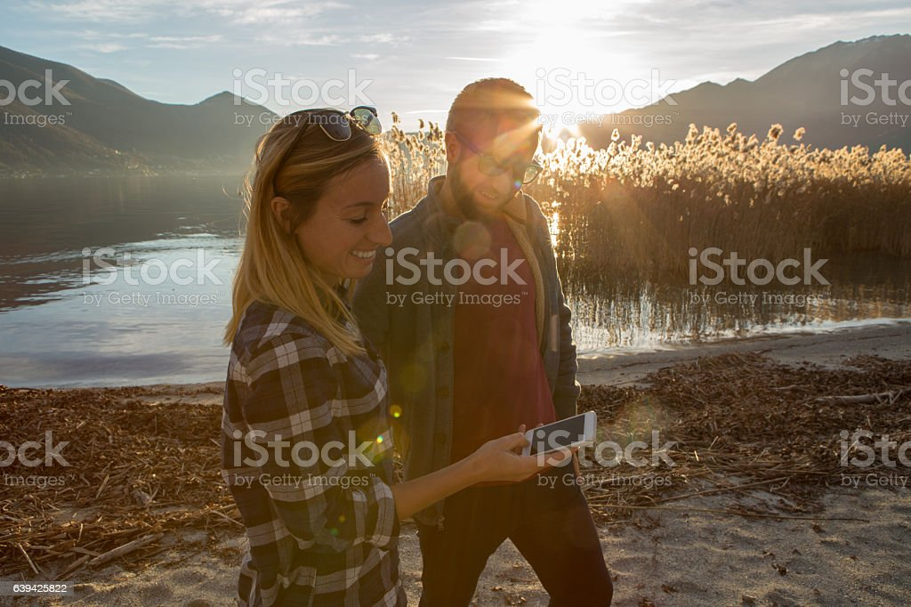 Young couple by the lake text messaging on phone stock photo