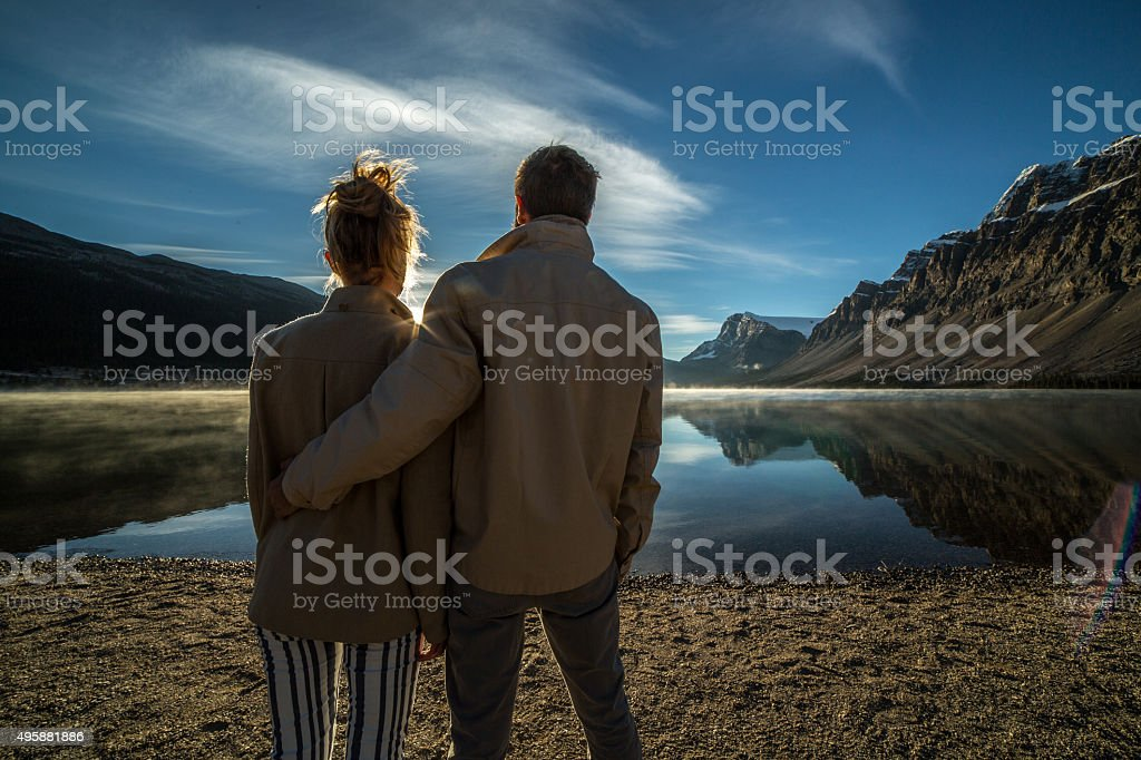 Young couple by the lake watching sunrise stock photo