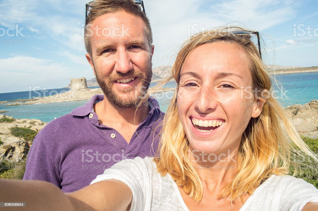 Young couple by the sea take a selfie portrait stock photo