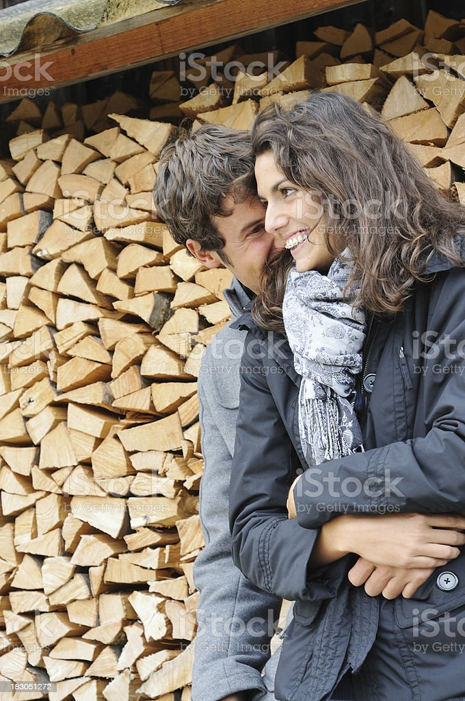 young couple by woodpile royalty-free stock photo