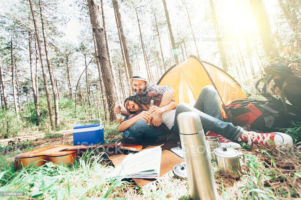 Young couple camping and leaning in front of tent stock photo