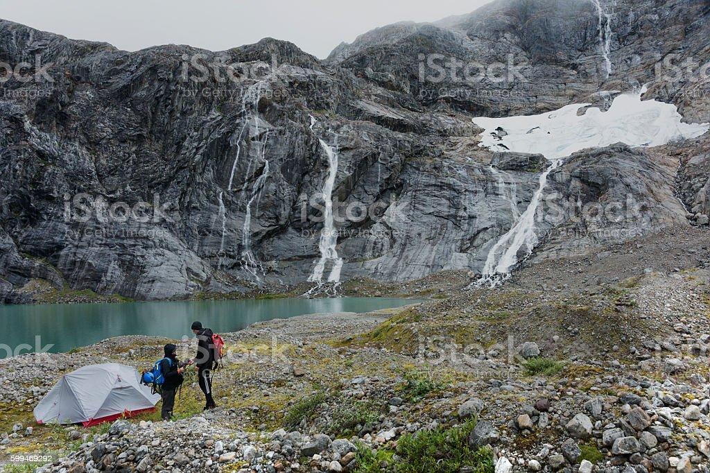 Young couple camping on Alaskan glacier stock photo