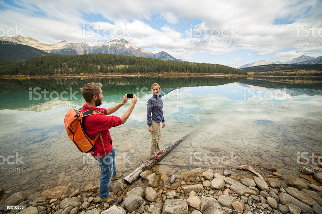 Young couple capturing autumn vacation moments stock photo