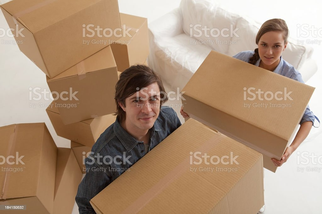 Young couple carrying cardboard boxes stock photo