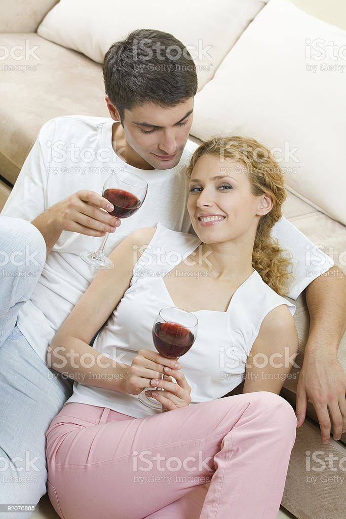 Young couple celebrating with red wine at home royalty-free stock photo