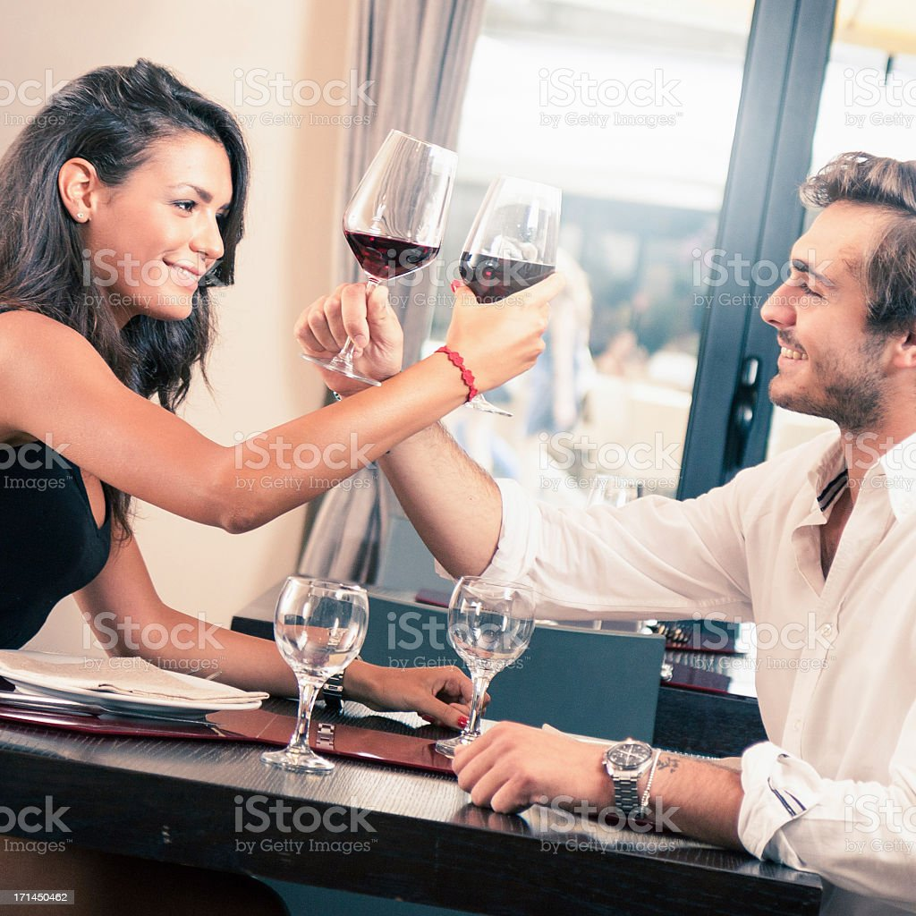Young couple celebrating with red wine at restaurant royalty-free stock photo