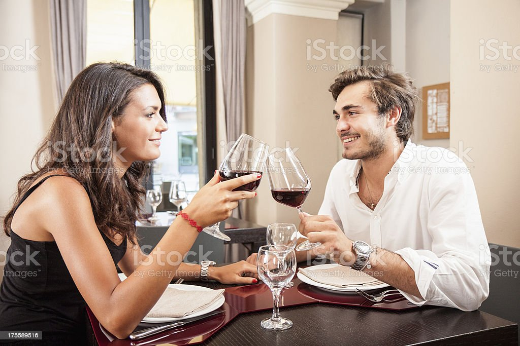 Young couple celebrating with red wine at restaurant stock photo