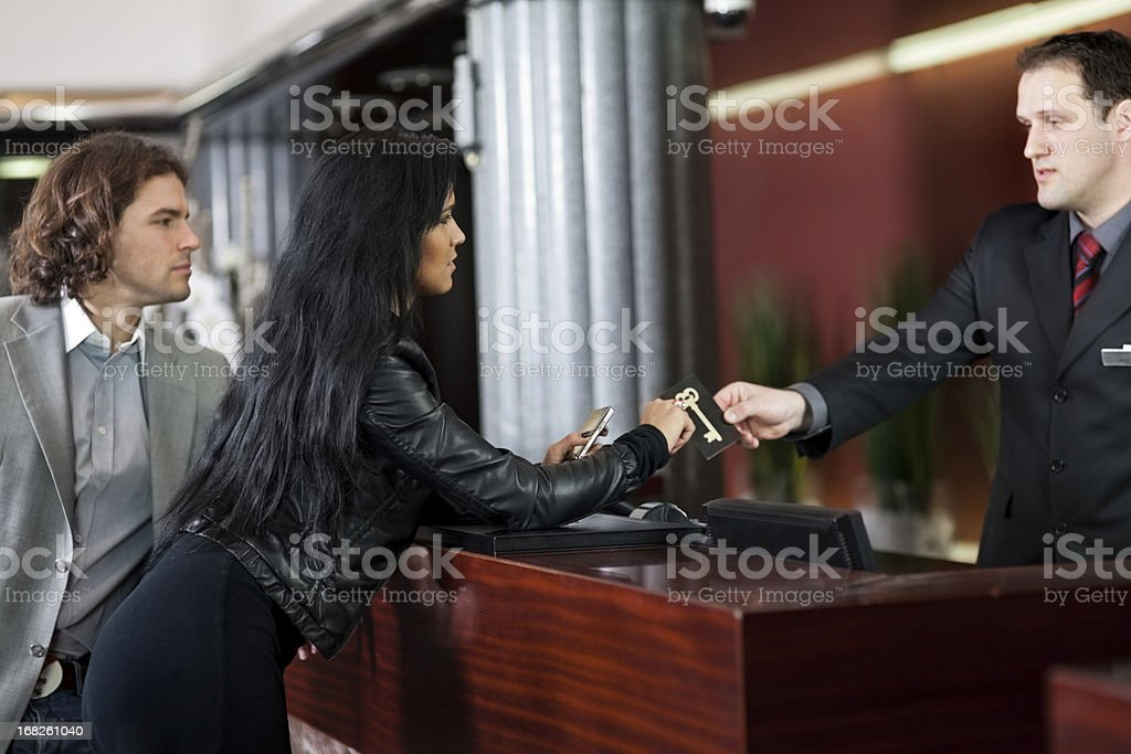 Young couple checking in to a hotel royalty-free stock photo