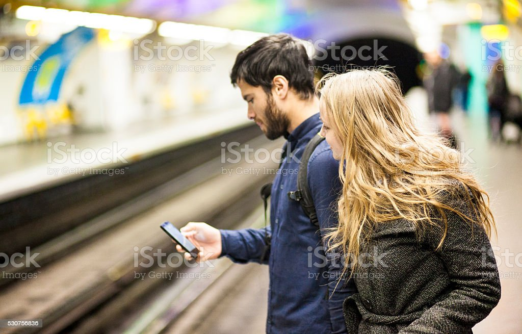 Young Couple Checking Train Arrival Times On Smartphone App stock photo