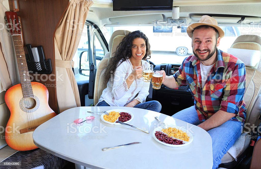 Young couple cheering inside of a caravan stock photo