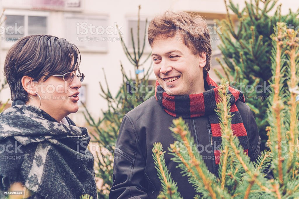 Young Couple Choosing Christmas Tree, City Market, Europe stock photo