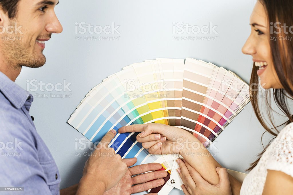 Young couple choosing paint swatches stock photo
