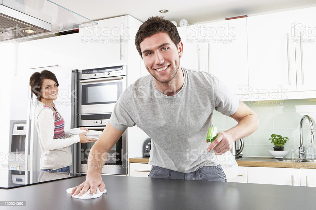 Young couple cleaning a modern kitchen stock photo