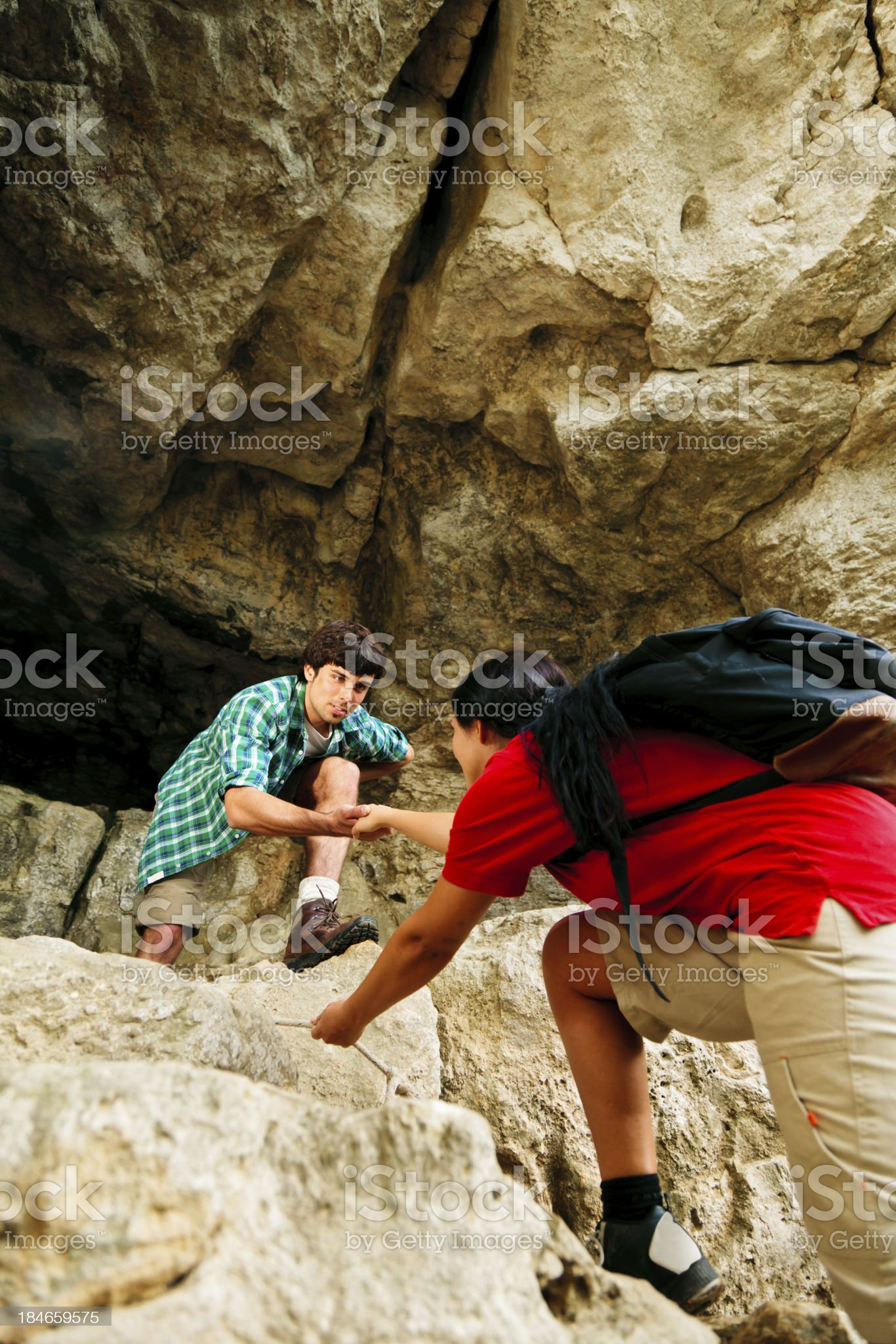 young couple climbing up a mountain royalty-free stock photo