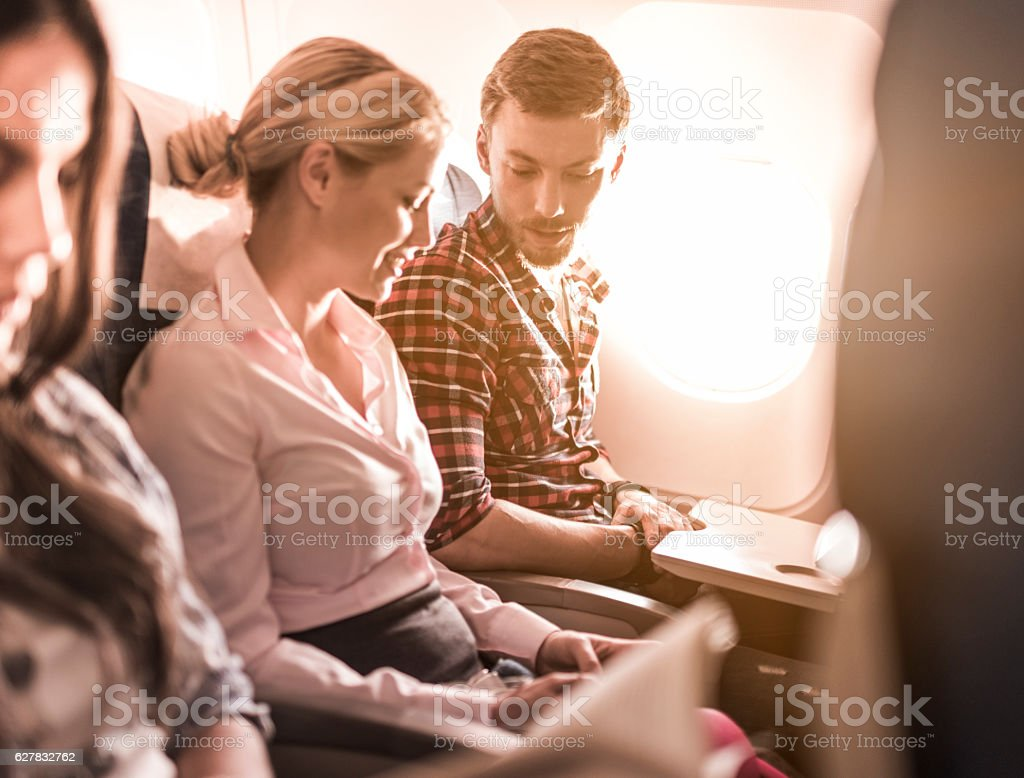 Young couple communicating while traveling by airplane. stock photo