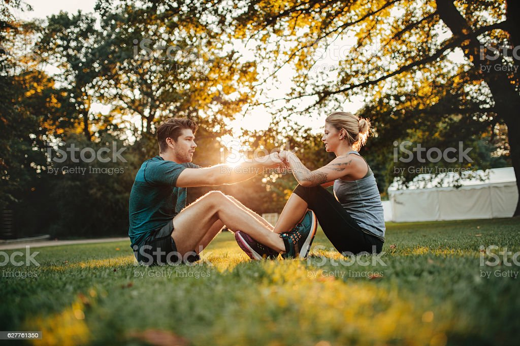 Young couple cooperating while stretching at park stock photo