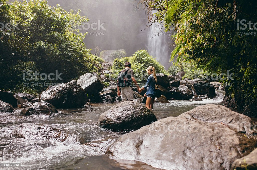 Young couple crossing stream in forest stock photo