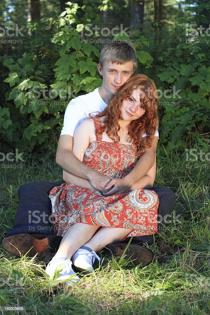 young couple cuddles red head girl front blonde boy back royalty-free stock photo