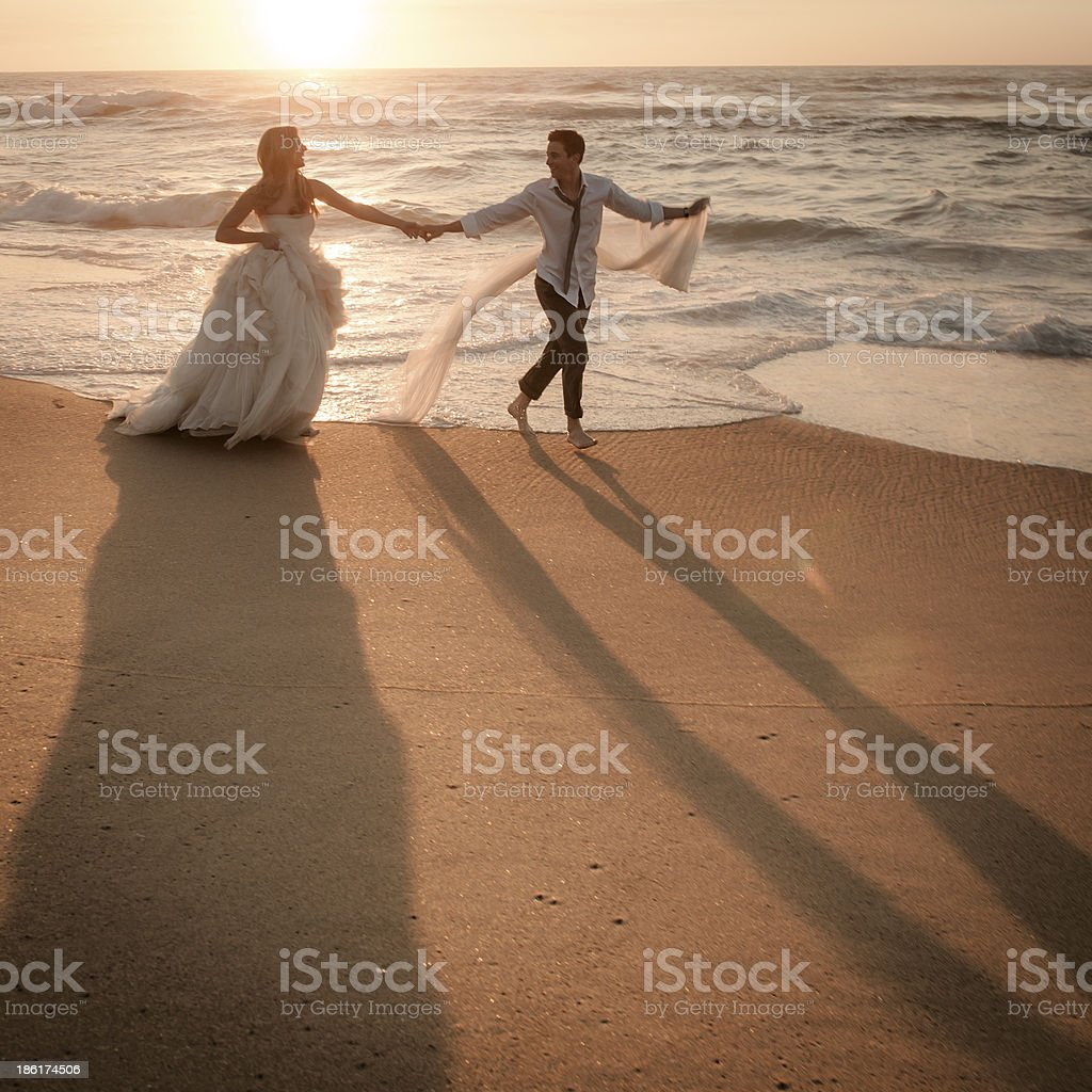 Young couple dancing along the sand at sunrise on beach royalty-free stock photo