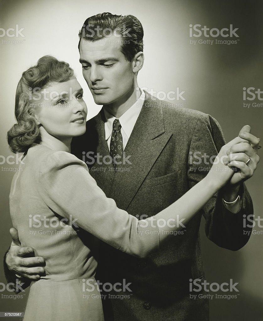 Young couple dancing in studio, (B&W) royalty-free stock photo