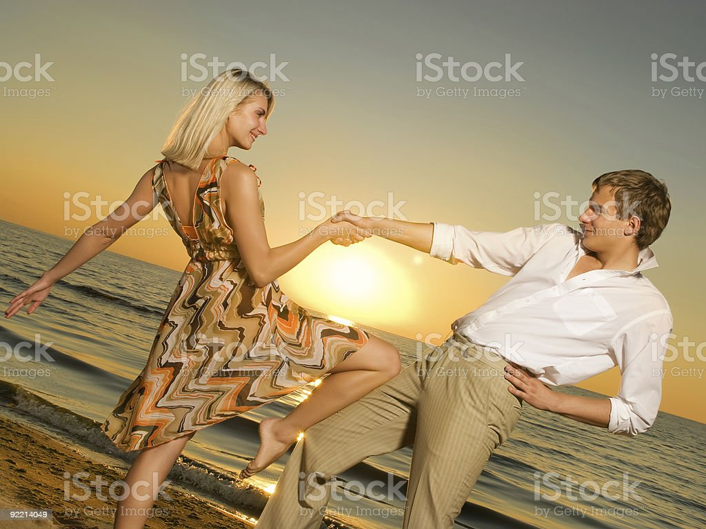 Young couple dancing near the ocean at sunset royalty-free stock photo