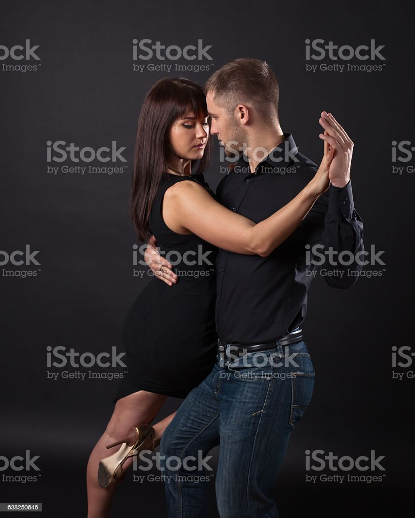 Young couple dancing on a dark background stock photo
