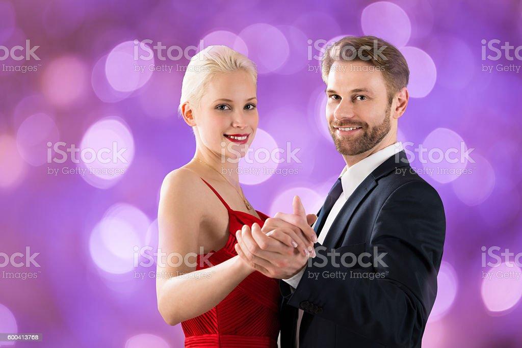 Young Couple Dancing On Bokeh Background stock photo