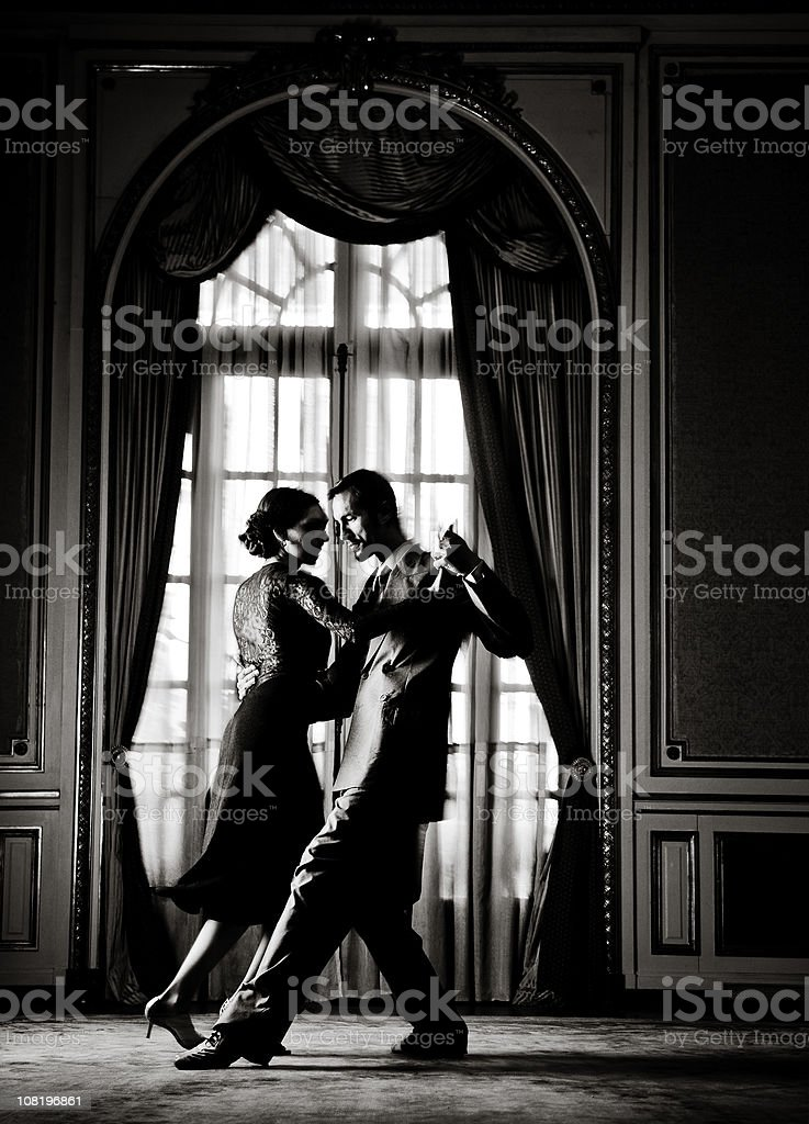 Young Couple Dancing Tango in Elegant Room, Toned stock photo