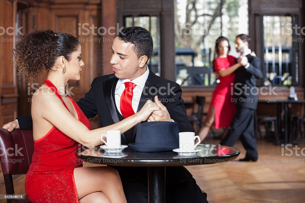 Young Couple Dating While Man And Woman Performing Tango stock photo