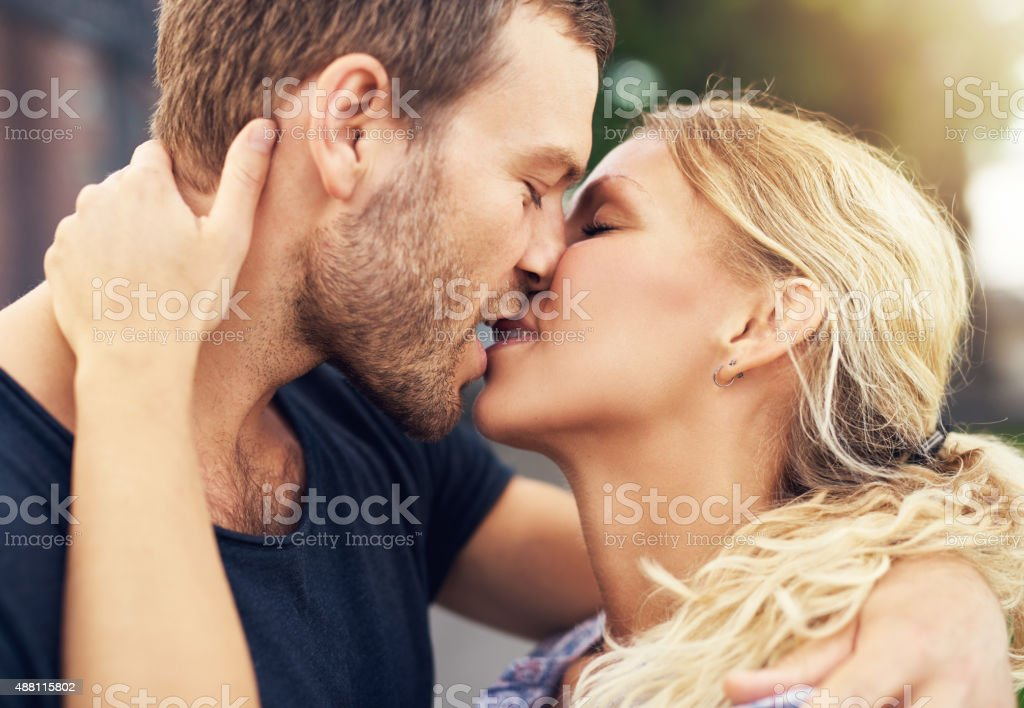 Young couple deeply in love sharing a romantic kiss, closeup profile...