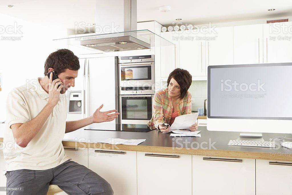 Young Couple Discussing Personal Finances In Modern Kitchen royalty-free stock photo