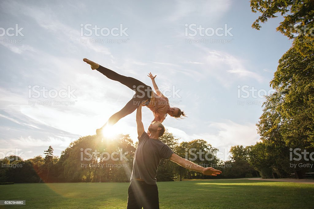Young couple doing acroyoga at the park stock photo