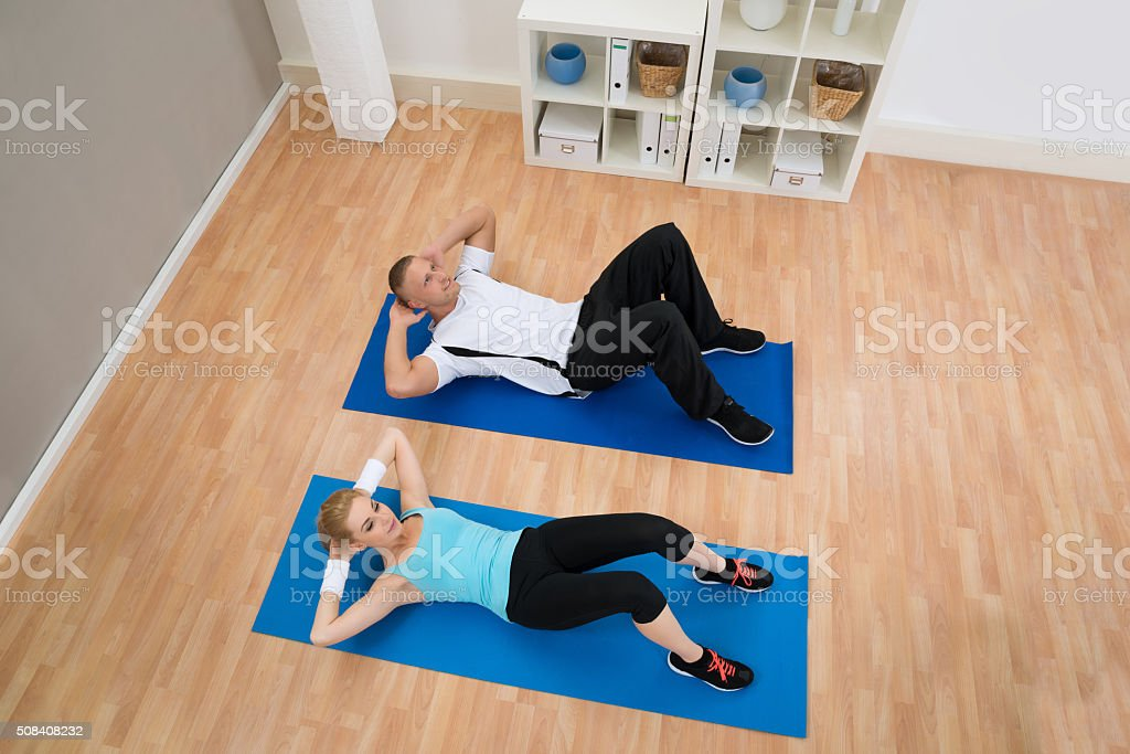 Young Couple Doing Crunches stock photo