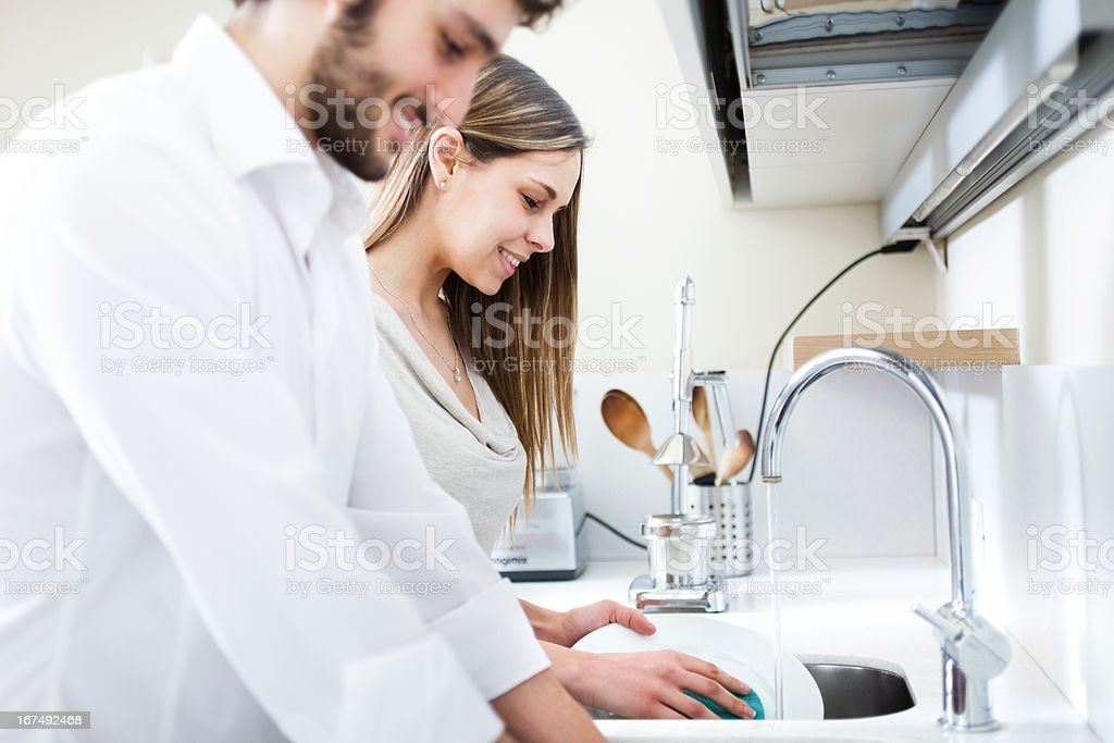 Young couple doing dishes stock photo