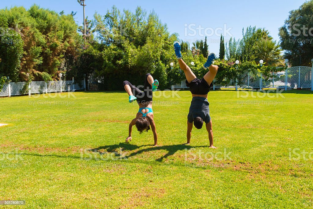 Young couple doing handstands training at the park in summer stock photo