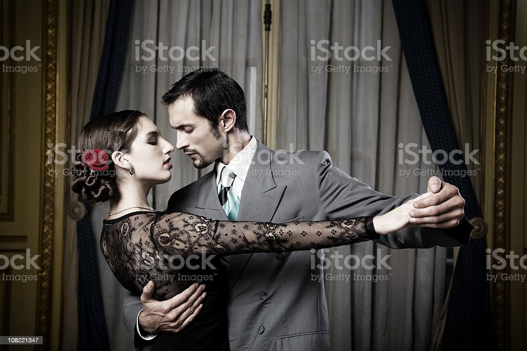 Young Couple Doing Tango Dance in Room, Low Key stock photo